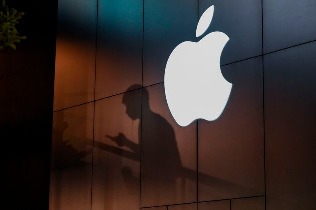 The shadow of a man is cast on the wall of an Apple store as he uses his mobile phone in Beijing on August...