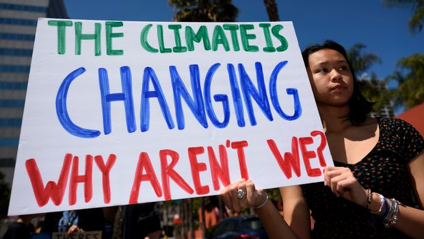 LOS ANGELES, CALIFORNIA, UNITED STATES - 2019/05/24: A protester is seen during a climate change demonstration holding a placard that says 'the climate is changing why aren't we?'. Students and environmental activists participate in a Climate Strike in Los Angeles, California. Organizers called on the Trump Administration to declare a state of climate emergency in order to save the planet, create a Green New Deal and transition into a zero emissions economy. (Photo by Ronen Tivony/SOPA Images/LightRocket via Getty Images)