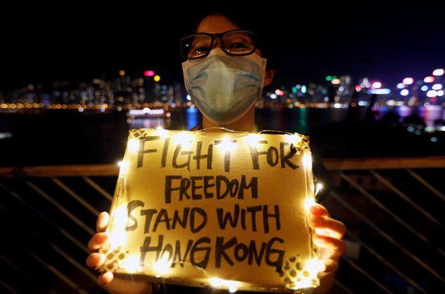 Hong Kong, le 23 août 2019. Une femme brandit une pancarte tandis que, le long de Tsim Sha Tsui...