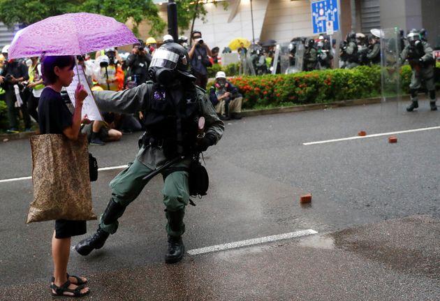 Un agent de la police anti-émeute s'approche d'une manifestante lors d'un rassemblement...