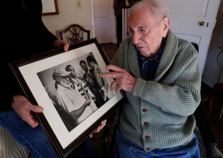 Hemingway's close friend and biographer A.E. Hotchner recounts the story of how he came to perform as a matador in a bullfight at the urging of Hemingway as he looks at a 1959 photograph taken at the event, Tuesday, Jan. 22, 2019, in Westport, Conn. In the photo, Ernest Hemingway is at far left, and Hotchner is second from right. The real matadors are Luis Miguel Dominguin, second from left, and Antonio Ordonez, far right. (AP Photo/Kathy Willens)