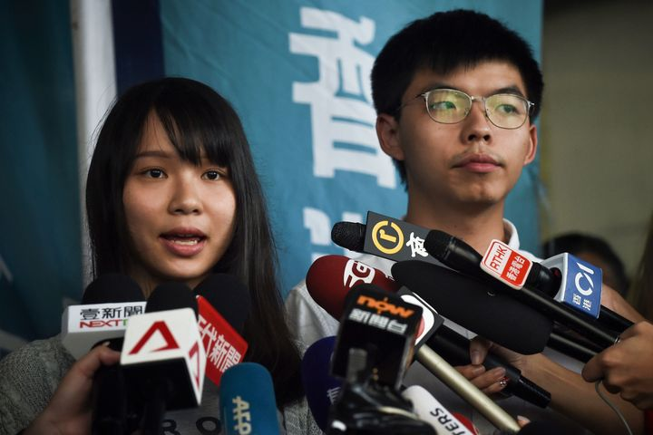 Pro-democracy activists Agnes Chow (L) and Joshua Wong (R) speak to the press after they were released on bail at the Eastern