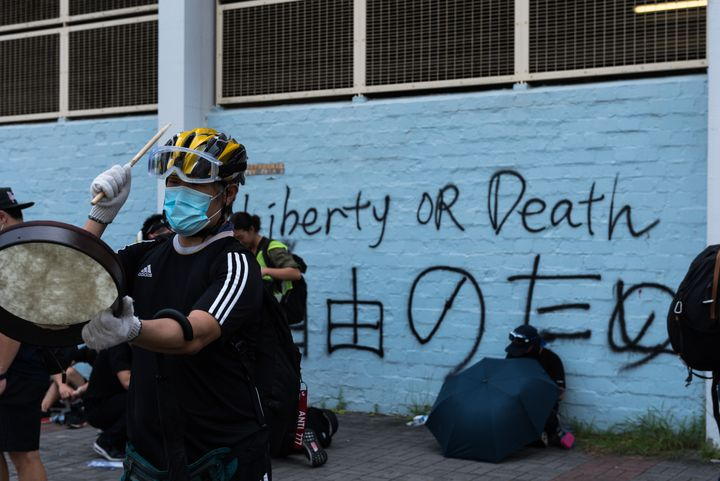 HONG KONG, CHINA - 2019/08/24: A protester drums in front of a wall with graffiti during the demonstration. Thousands of anti