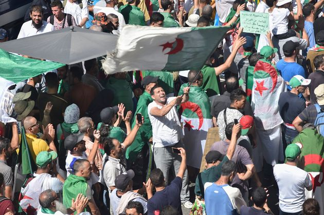 A protester waves a national flag during a demonstration against the ruling class in Algeria's capital...