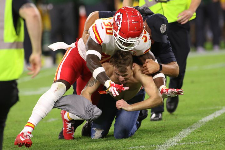 Kansas City Chiefs defensive back Harold Jones-Quartey helps the Green Bay Police Department tackle a fan who ran on the fiel