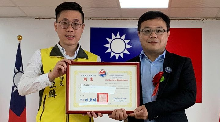 In this photo taken June 20, 2019, Lee Meng-chu, right, accepts a certificate from Archer Chen, left, Chief of Fangliao Towns
