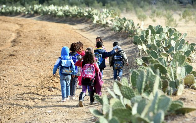 TO GO WITH AFP STORY BY INES BEL AIBA - Tunisian children carry their schoolbags as they are heading...