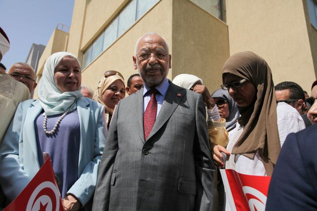Leader of Ennahda party Rached Ghannouchi (C) poses for photos as he arrives to the Independent High...