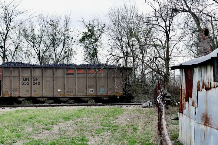 Carloads of uncovered coal product sit for hours in Harriman Park.