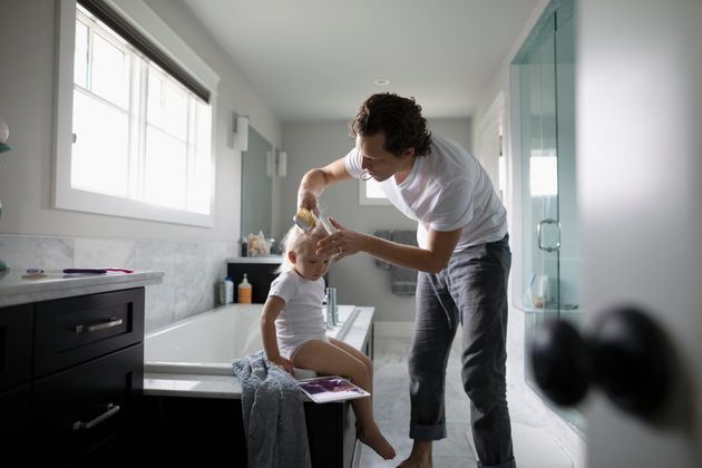 A man brushes a toddler's hair in a bathroom.
