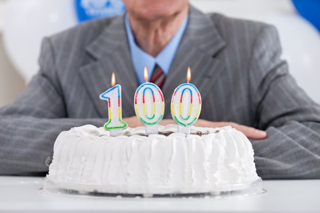 birthday cake with lit candles for a century, one hundredth