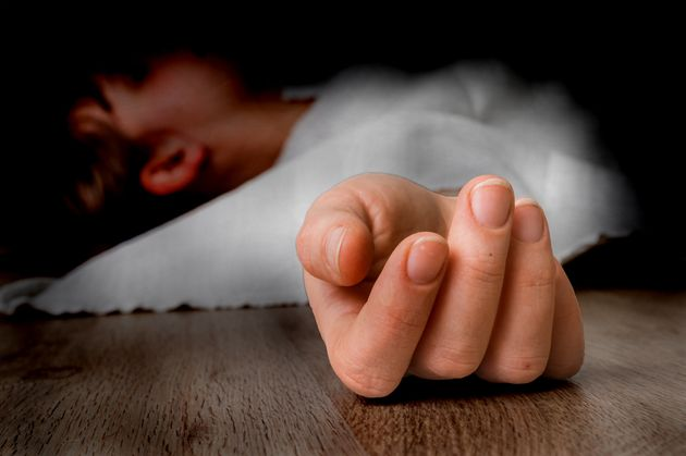 Dead woman lying on the floor under white cloth with focus on