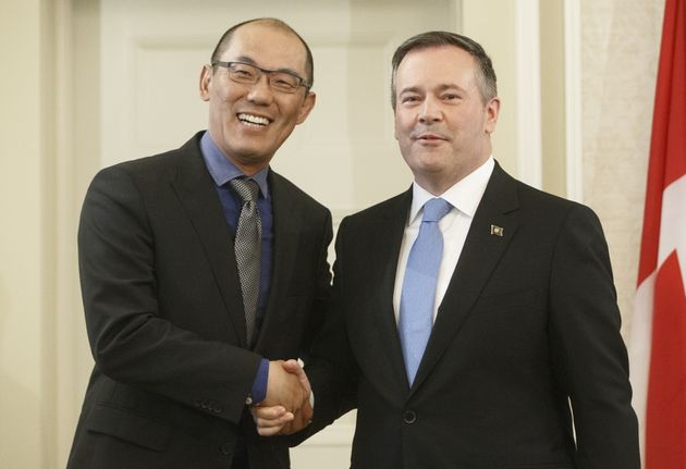 Alberta Premier Jason Kenney shakes hands with Jason Luan, associate minister of mental health and addictions...