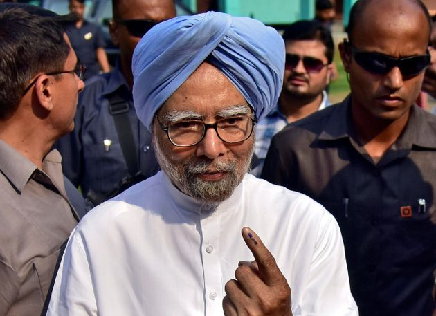 India's former Prime Minister Manmohan Singh shows his ink-marked finger after casting his vote at a...