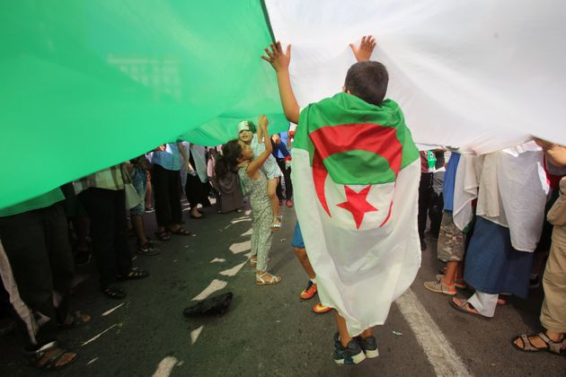 Demonstrators carry a national flag during a protest demanding social and economic reforms, as well as...
