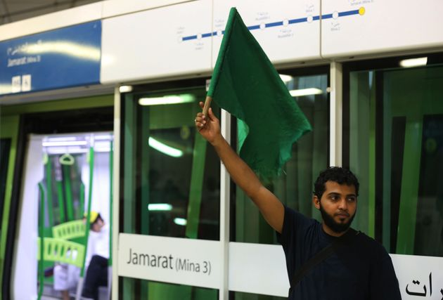 IMAGE USED FOR REPRESENTATIONAL PURPOSES ONLY. (A railway usher raises a green flag to Muslim pilgrims...