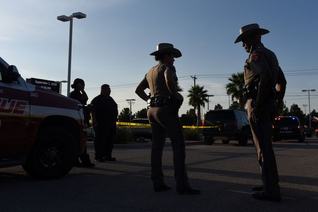 State troopers and other emergency personnel monitor the scene at a local car dealership following a...