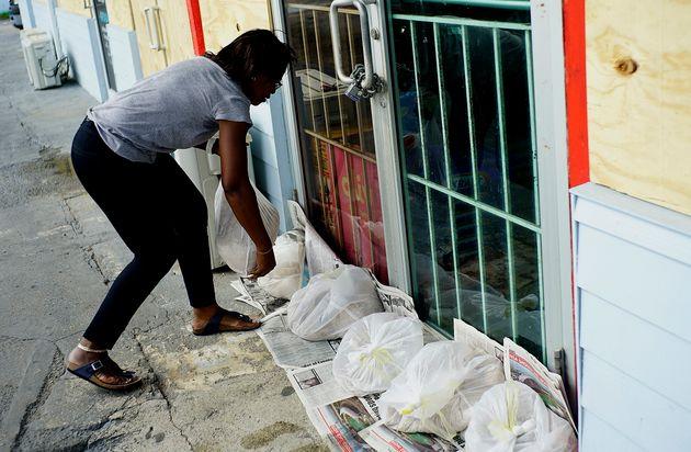 Yolande Rolle utiliza sacos de areia para impedir invasão da água das tempestades causadas...