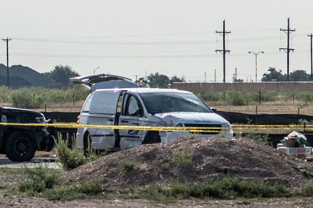 A damaged police vehicle and U.S. Postal Service van are seen blocked off with tape near where a gunman...