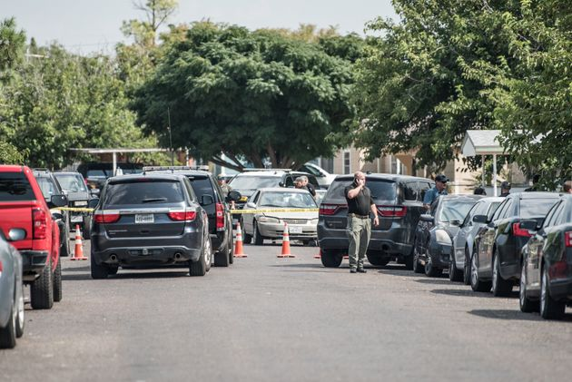 Officers inspect a car in the aftermath of Saturday's deadly shooting in Odessa,