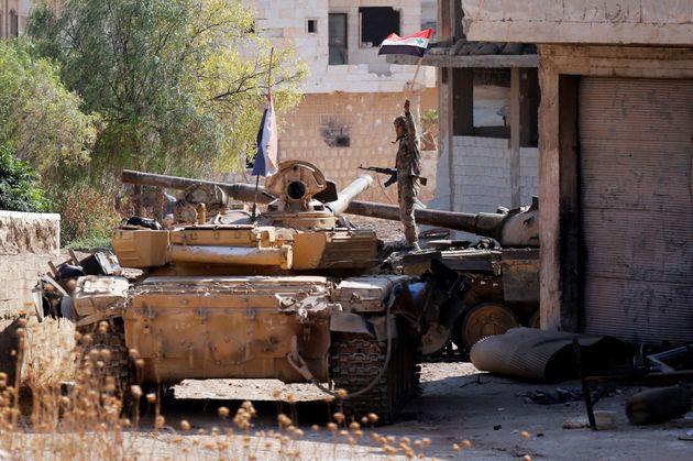 Un militaire syrien brandit un drapeau à Idleb, le 24 août