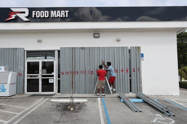 Workers place shutters over the windows of a Food Mart store in Riviera Beach, Florida.