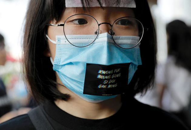A woman wears a face mask and a sticker reading