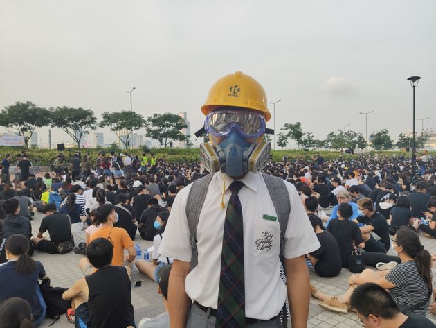 HONG KONG, CHINA - AUGUST 22: A high-school student, wearing a helmet and a face-mask, is seen at a rally...
