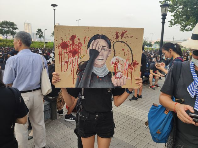 HONG KONG, CHINA - AUGUST 22: A high-school student holds an image, depicting a woman who lost an eye,...