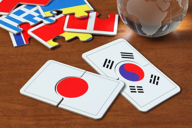 puzzle with the national flag of Japan and Korea on wooden