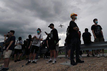 A plane flies over anti-extradition bill protesters as they demonstrate outside the airport in Hong