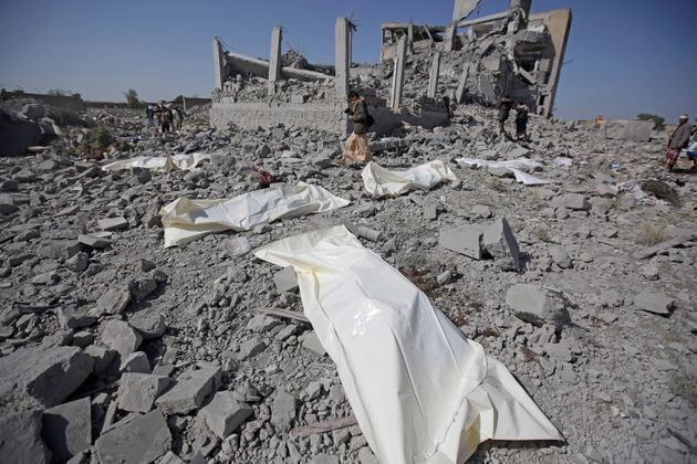 Bodies lie on the ground after being recovered from under the rubble of a Houthi detention center destroyed...