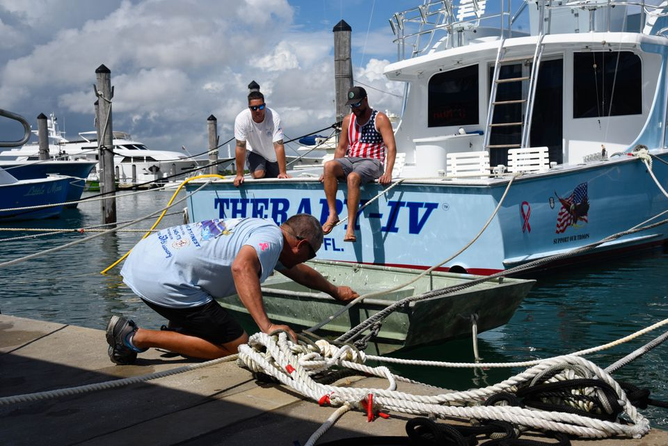 Boat workers Chris Bostwick, Mark and Mike Rodgriguez secure a boat at Haulover Marina in Haulover Beach,...