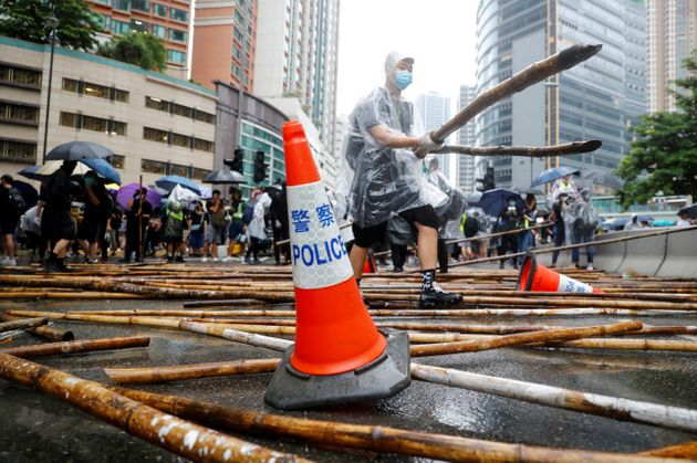 A demonstrator helps to build a barricade during a protest in Tsuen Wan, in Hong Kong, China August 25,...