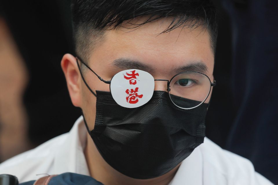 A secondary student covers one eye reading