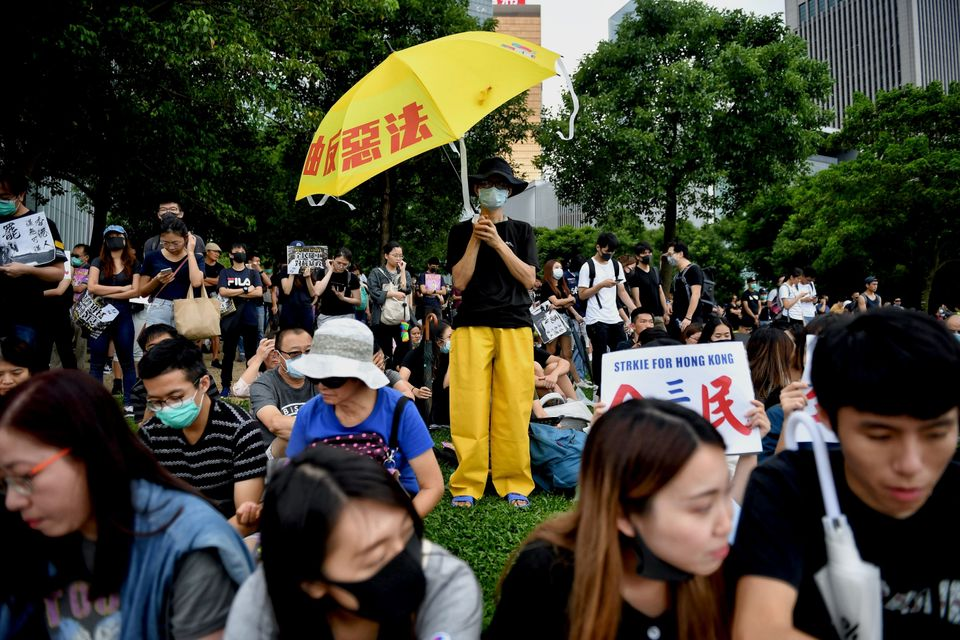 TOPSHOT - A protester (C) holds an umbrella in the latest rally against a controversial extradition bill...