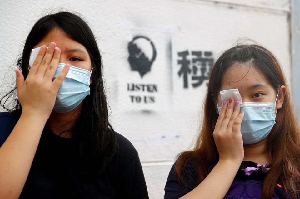Students cover their eyes as they protest at Edinburgh Place in Hong Kong, China September 2, 2019. REUTERS/Kai