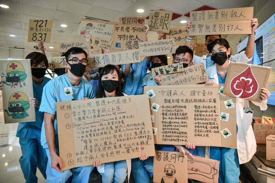 TOPSHOT - Medical staff hold placards after they formed a human chain to express solidarity with anti-extradition...