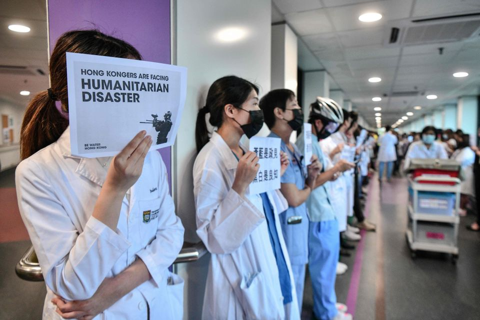 Medical staff hold posters as they form a human chain to express solidarity with anti-extradition bill...
