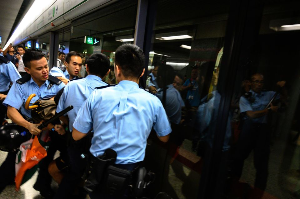 TOPSHOT - A man is arrested at the Lok Fu MTR station during a train disruption protest in Hong Kong...