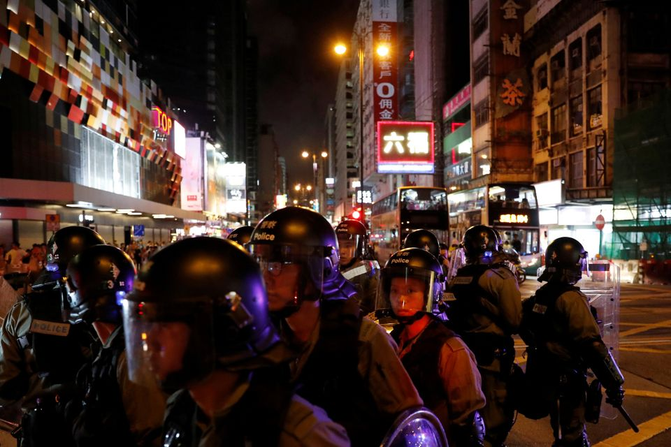 Riot police patrol streets near Mong Kok police station during an anti-extradition bill protest, in Hong...