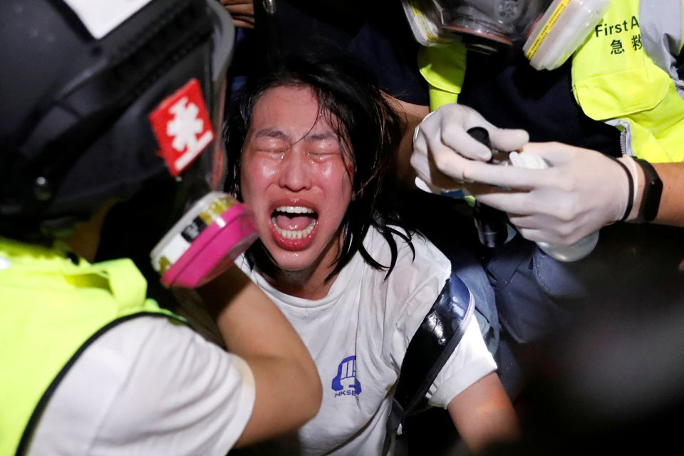 An anti-extradition bill protester receives medical attention after tear gas and pepper spray was used...