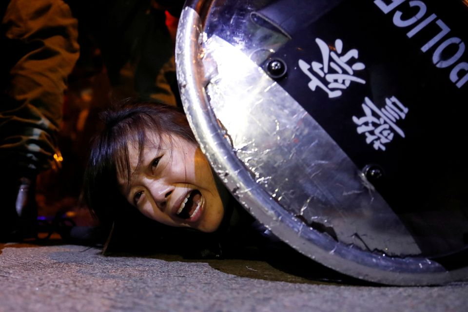 An anti-extradition bill protester is detained by riot police during a protest outside Mong Kok police...