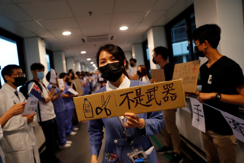A healthcare staff holds a placard which reads