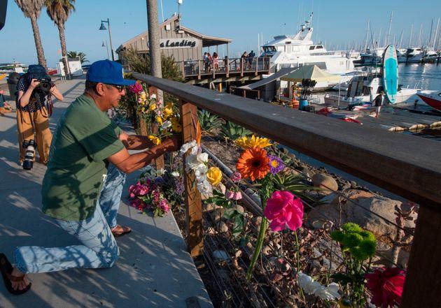 ボート火災で亡くなった方のため、献花する男性