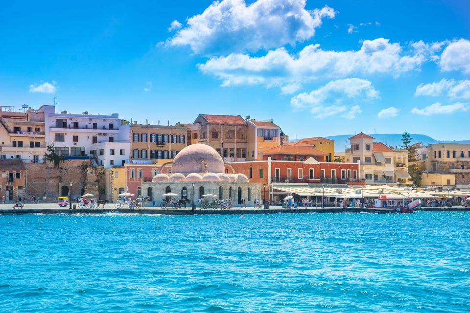 View of the old harbor of Chania with horse carriages and mosque, Crete,