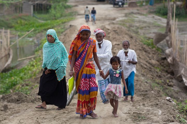 Villagers walk towards a National Register of Citizens (NRC) center to check their names on the final list in Pabhokati village in Morigaon district, in the northeastern Indian state of Assam, Saturday, Aug. 31, 2019. India has published the final citizenship list in the Indian state of Assam, excluding nearly two million people amid fears they could be rendered stateless. The list, known as the National Register of Citizens (NRC), intends to identify legal residents and weed out illegal immigrants from the state. (AP Photo/Anupam Nath)