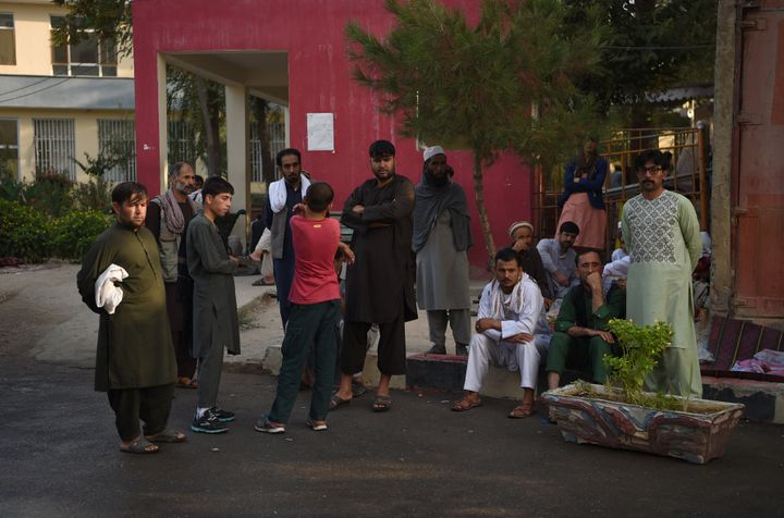 Relatives of Afghan victims wait outside the Wazir Akbar Khan hospital after a massive explosion the night before in Kabul on