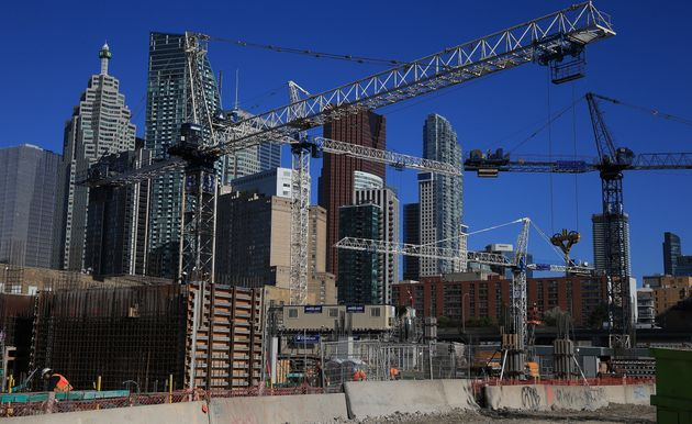 Construction cranes fill the sky at a site at Queen's Quay in Toronto, June