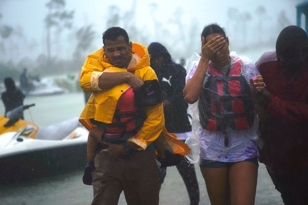 A family with a small child is escorted to a safety zone amid flooding in Freeport on Tuesday.